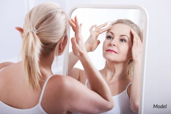 Woman looking at her face in mirror after a facial procedure, such as facelift surgery.
