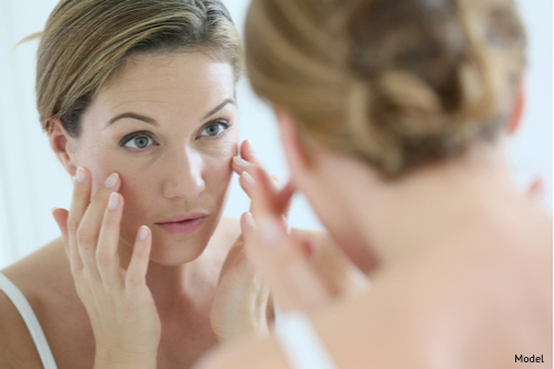 Woman in her 30s looking in mirror, wondering if she could benefit from a facelift.