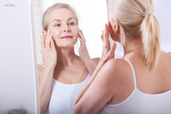 Middle aged woman looking at wrinkles in mirror. Before-after anti-aging facelift treatment.