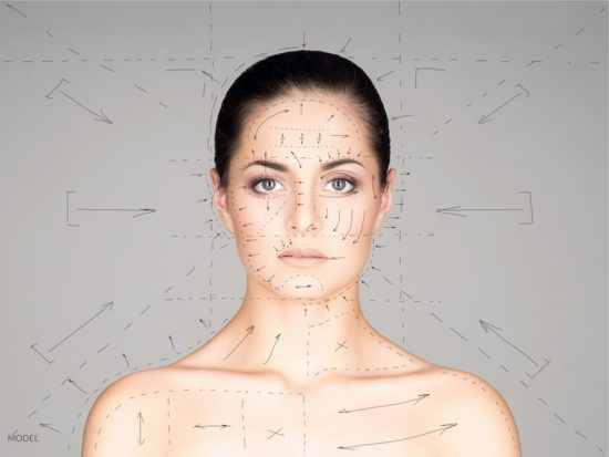 Young woman with lines drawn around and on her face. Cosmetic surgery concept.